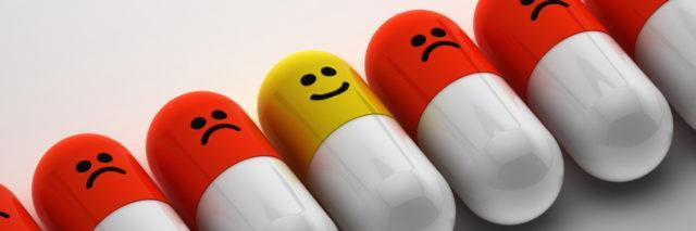 A row of pills with sad faces, with one with a smiley face in the middle