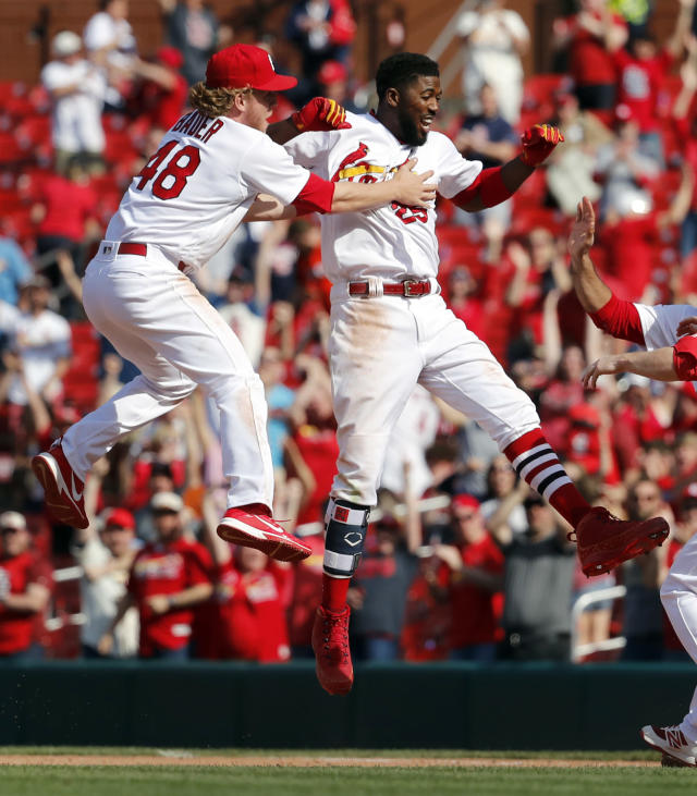 St. Louis Cardinals' Dexter Fowler,right, is congratulated by teammates after hitting a walkoff single during the 13th inning of a baseball game against the New York Mets, Thursday, April 26, 2018, in St. Louis. (AP Photo/Jeff Roberson)
