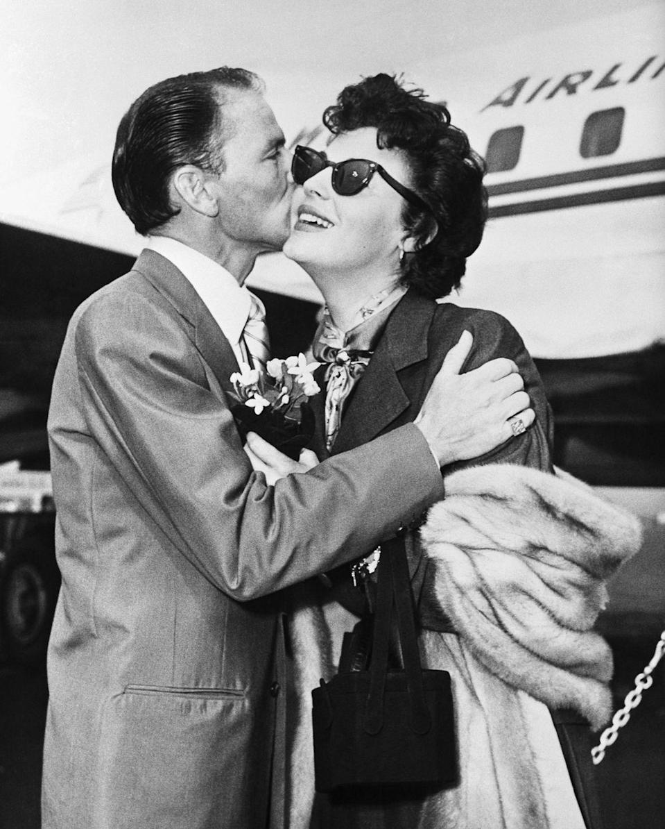 <p>Gardner, arriving for a movie premiere during the same year she was awarded a star on the Hollywood Walk of Fame, is greeted by Sinatra at the Idlewild airport while wearing a classic trench, silk neck scarf, and cat-eye sunglasses. <br></p>