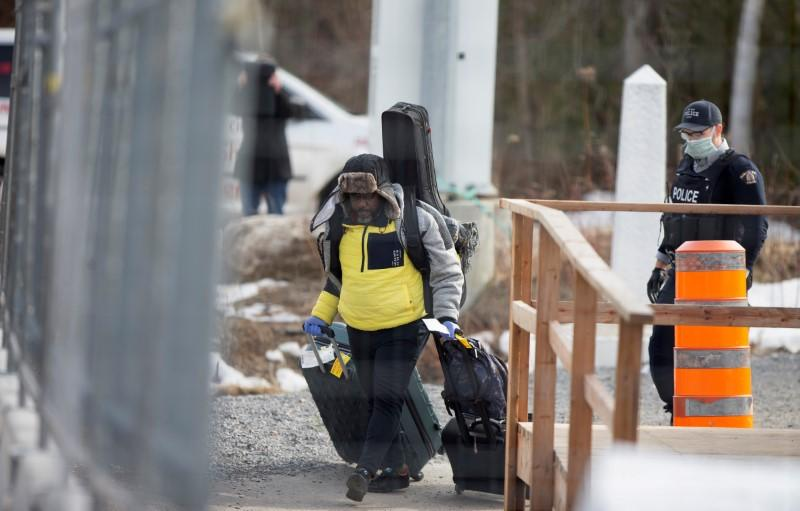 FILE PHOTO: An asylum seeker crosses the border from New York into Canada at Roxham Road in Hemmingford Quebec
