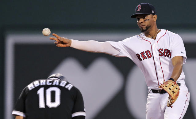 Chicago White Sox 's Yoan Moncada (10) ducks as Boston Red Sox shortstop Xander Bogaerts, right, fires the ball while turning a double play during the fifth inning of a baseball game at Fenway Park in Boston, Monday, June 24, 2019. (AP Photo/Charles Krupa)