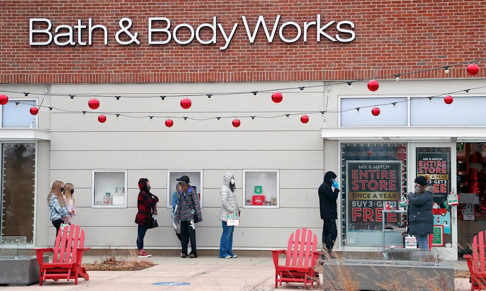 A socially distanced line of customers wait to shop at Bath & Body Works during Black Friday shopping outdoors at Deer Park Town Center Friday, Nov. 27, 2020, in Deer Park, Ill.