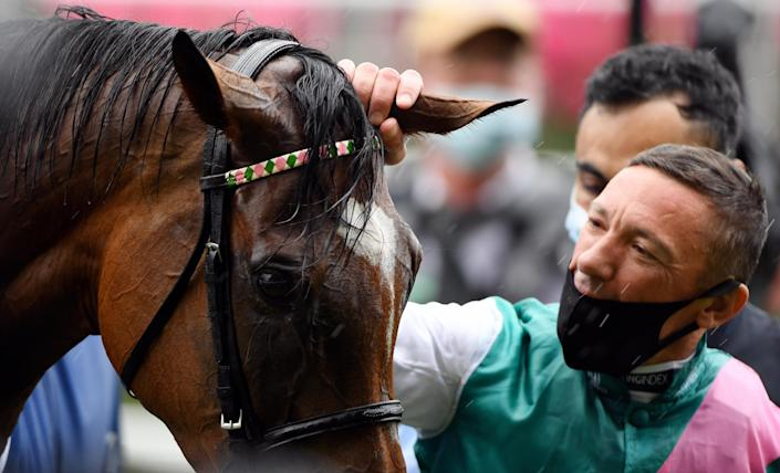 Frankie Dettori strokes Enable as they celebrate winning the King George VI and Queen Elizabeth QIPCO Stakes at a rainy Ascot