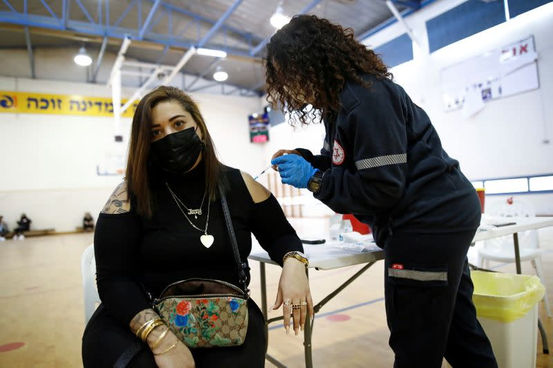 A woman is vaccinated against the coronavirus disease (COVID-19) at a temporary vaccination centre at a sports court in Tel Aviv