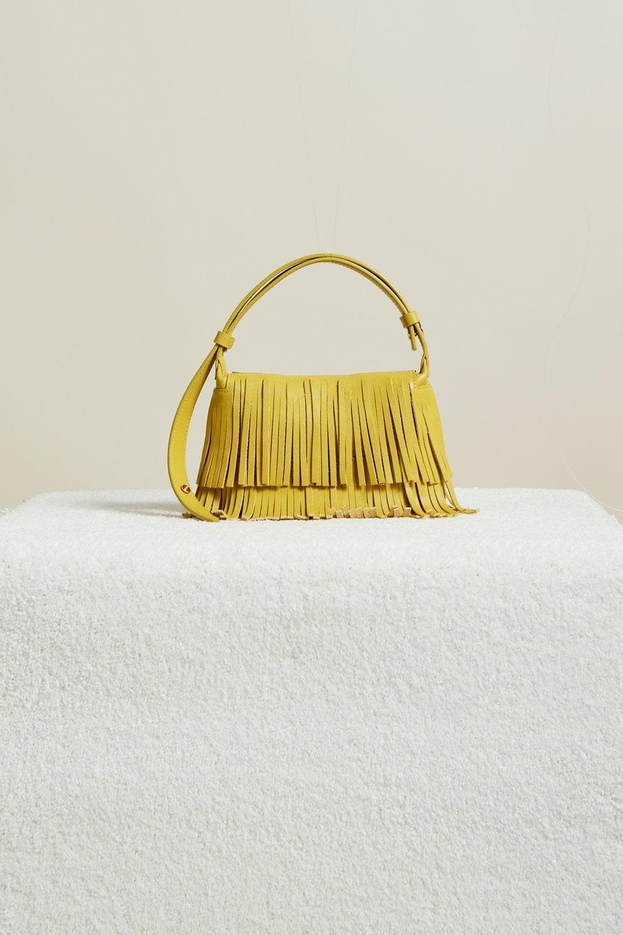 <p>There's no way you haven't seen Simon Miller's colorful bucket bags yet. The brand is not only spotted on celebrities and influencers, but conserves water during production by using organic mills and ozone technology.</p> <p><strong>What We'd Buy</strong>: <span>Simon Miller Mini Puffin in Chartreuse Fringe</span> ($320)</p>