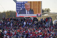 A throng of supporters listen to a video message as they await President Donald Trump for a campaign stop, Saturday, Oct. 31, 2020, at the Butler County Regional Airport in Butler, Pa. (AP Photo/Keith Srakocic)