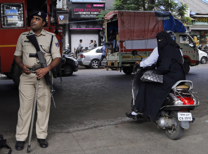 A police officer stands guards on a street in Mumbai, Saturday, Nov. 9, 2019. India's security forces were on high alert ahead of the Supreme Court's verdict Saturday in a decades-old land title dispute between Muslims and Hindus over plans to build a Hindu temple on a site where Hindu hard-liners demolished a 16th century mosque in 1992, sparking deadly religious riots. India's state broadcaster says that the country's top court rules disputed religious ground in favor of Hindus with alternate land for Muslims. (AP Photo/Rajanish Kakade)
