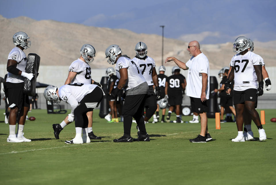 Las Vegas Raiders offensive line coach Tom Cable, second right, directs his players to run drills during an NFL football practice Saturday, July 31, 2021, in Henderson, Nev. (AP Photo/David Becker)