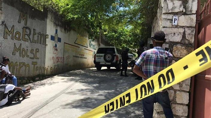 """Journalists stand next to a yellow police cordon near the residence of Haiti""""s President Jovenel Moise after he was shot dead by unidentified attackers, in Port-au-Prince, Haiti July 7, 2021."""