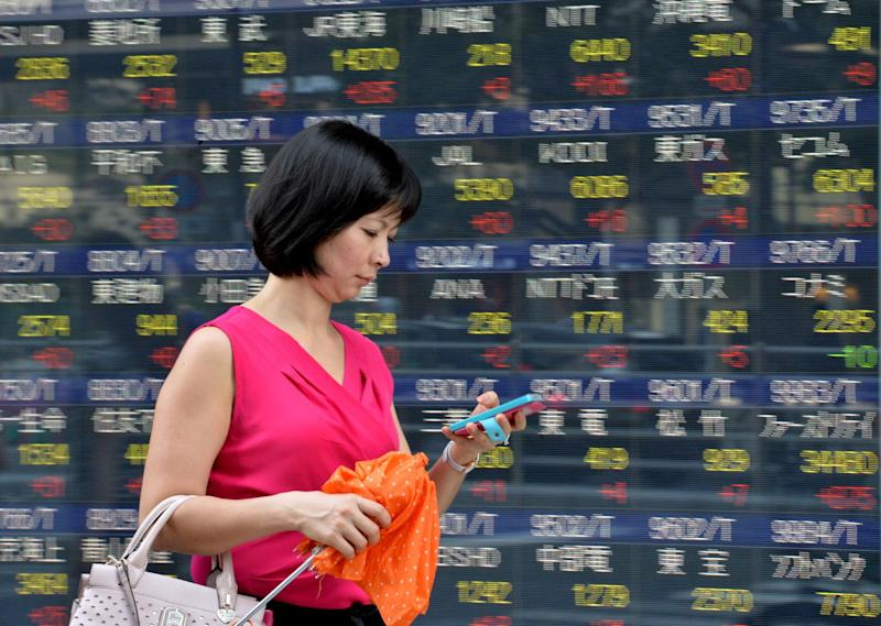 A pedestrian passes before a share prices board in Tokyo on June 19, 2014