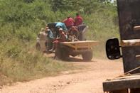 Artisanal miners ride on the back of a truck on their way to a wildcat gold mine in El Callao, Venezuela August 8, 2018. REUTERS/William Urdaneta/Files
