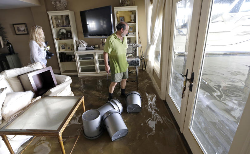 Kenny Melkin, right, and his wife Becky return home to see the flood damage caused by Isaac in the West End Park neighborhood along Lake Pontchartrain, Friday, Aug. 31, 2012 in New Orleans. Isaac crawled into the central U.S. on Friday, leaving behind a soggy mess in Louisiana. It will be a few days before the water recedes and people in flooded areas can return home. New Orleans itself was spared, thanks in large part to a levee system fortified after Katrina devastated the Gulf Coast in 2005. (AP Photo/David J. Phillip)