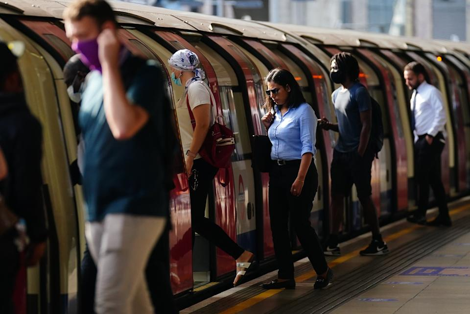 Commuters, some not wearing facemasks, getting on a Jubilee Line train at 0843 at Canning Town station, London, after the final legal Coronavirus restrictions were lifted in England. Picture date: Monday July 19, 2021. (Photo by Victoria Jones/PA Images via Getty Images)