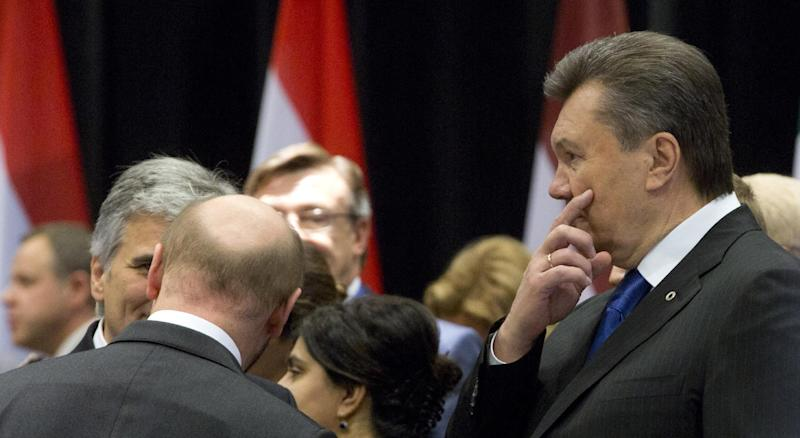 Ukrainian President Viktor Yanukovych, right, arrives for a plenary session at an Eastern Partnership Summit in Vilnius on Friday, Nov. 29, 2013. The European Union is extending its geopolitical reach eastward by sealing association agreements with Georgia and Moldova, but has missed out on a landmark deal with Ukraine as its key objective. (AP Photo/Virginia Mayo)