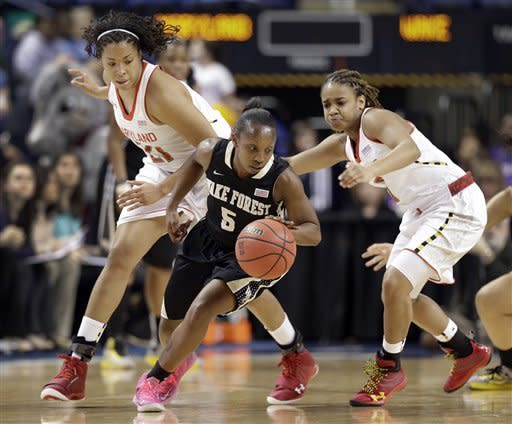 Wake Forest's Chelsea Douglas, center, escapes a trap by Maryland's Tianna Hawkins, left, and Brene Moseley, right, during the first half of an NCAA college basketball game at the Atlantic Coast Conference tournament in Greensboro, N.C., Friday, March 8, 2013. (AP Photo/Chuck Burton)