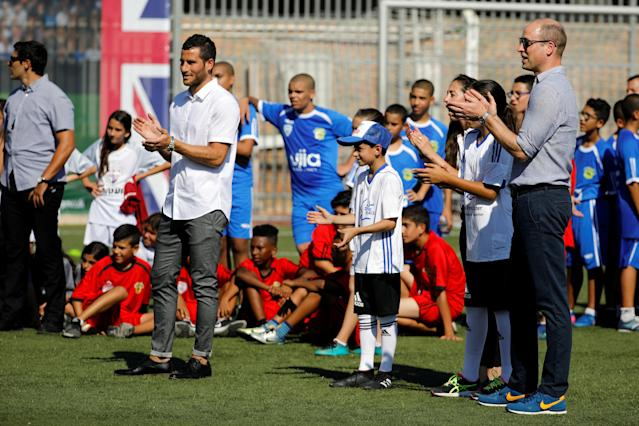 Britain's Prince William applauds as he stands with Tomer Hemed, an Israeli professional footballer who plays as a striker for English Premier League club Brighton & Hove Albion during a soccer event with Jewish, Muslim and Christian children organized by The Equalizer and Peres Center for Peace in Jaffa, near Tel Aviv, Israel, June 26, 2018. REUTERS/Amir Cohen