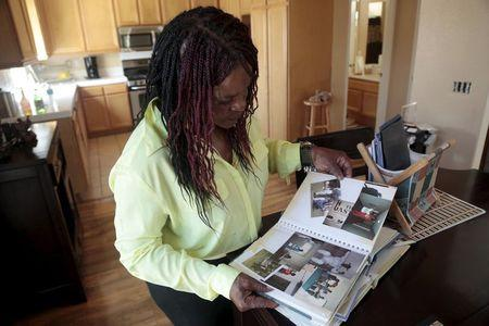 Vanessa White, who has lost multiple family members in gun shootings, looks through family photos at her home in Compton, California June 26, 2015. REUTERS/Jonathan Alcorn