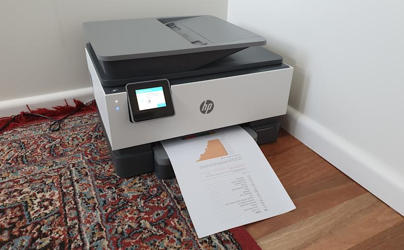 HP OfficeJet Pro 9010 printer with paper coming out of it.