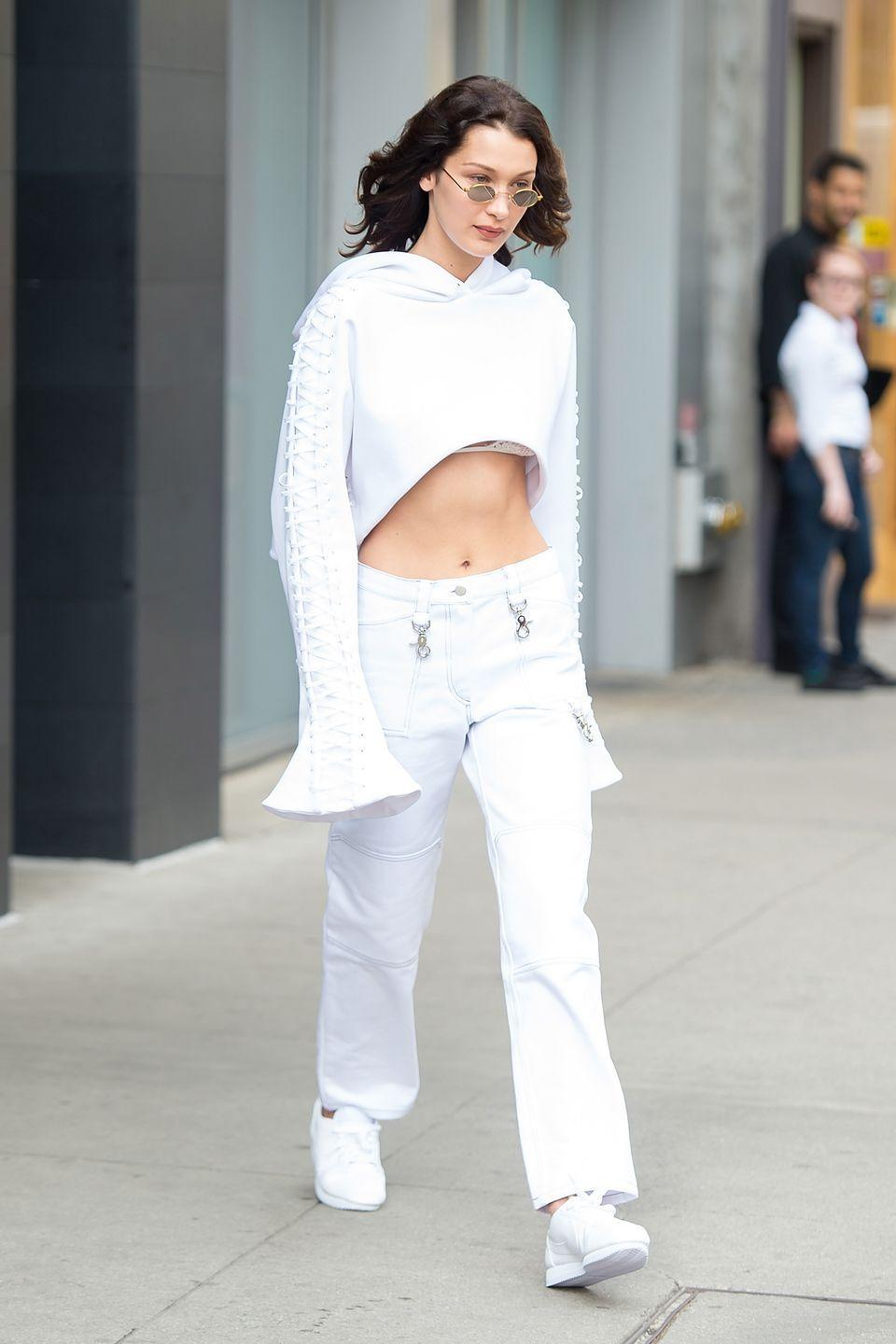 <p>In a white cropped sweatshirt, Brashy Gotland pants, white sneakers and Roberi & Fraud sunglasses while out in New York. </p>
