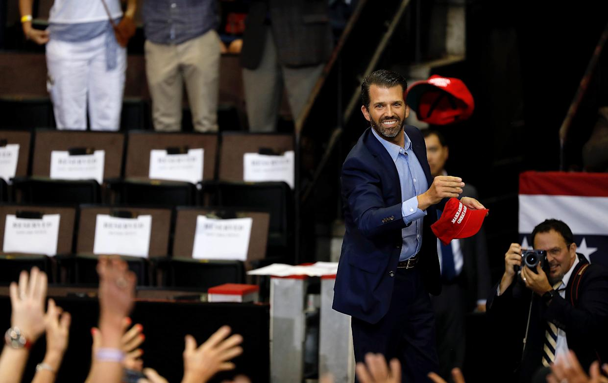 Donald Trump Jr. throws Make America Great Again hats to the crowd during a rally at U.S. Bank Arena Thursday, August 1, 2019, in downtown Cincinnati.
