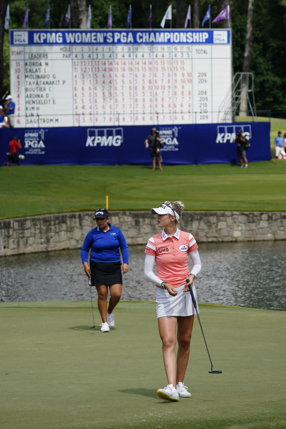 Nelly Korda of the U.S., right, and Lizette Salas, also of the U.S., walk off the course after finishing on the 18th hole, during the third round of play in the KPMG Women's PGA Championship golf tournament, Saturday, June 26, 2021, in Johns Creek, Ga. (AP Photo/John Bazemore)