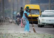 A woman cleans a street in Lagos