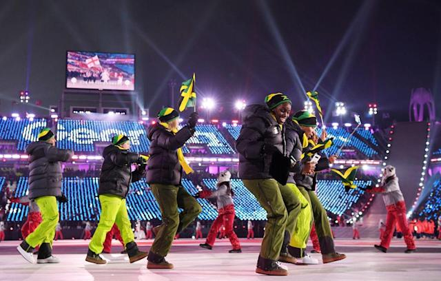 <p>Flag bearer Audra Segree of Jamaica and teammates wear bright green pants, black puffer jackets, and beanies with their nation's flag on them while entering the stadium during the opening ceremony of the 2018 PyeongChang Games. (Photo: Matthias Hangst/Getty Images) </p>