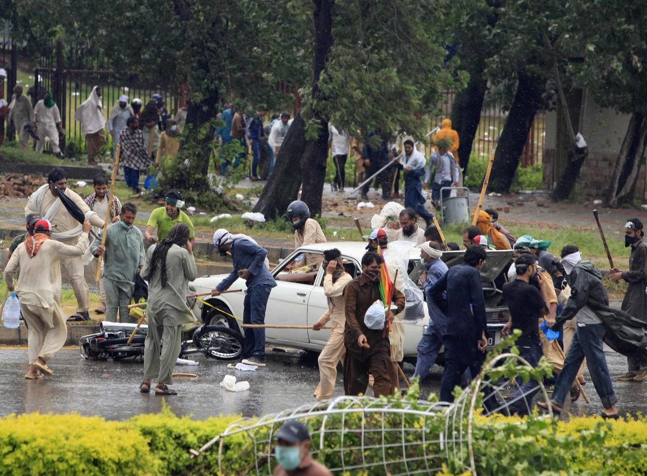 Supporters of Tahir ul-Qadri, Sufi cleric and leader of political party Pakistan Awami Tehreek (PAT), use sticks to hit a car and a motorcycle as they protest during Revolution March towards the prime minister's house in Islamabad September 1, 2014. Pakistani protesters pushed closer to the prime minister's house in central Islamabad on Monday in their bid to force his removal and forced national television off the air after clashes turned violent over the weekend. REUTERS/Faisal Mahmood (PAKISTAN - Tags: POLITICS CIVIL UNREST)