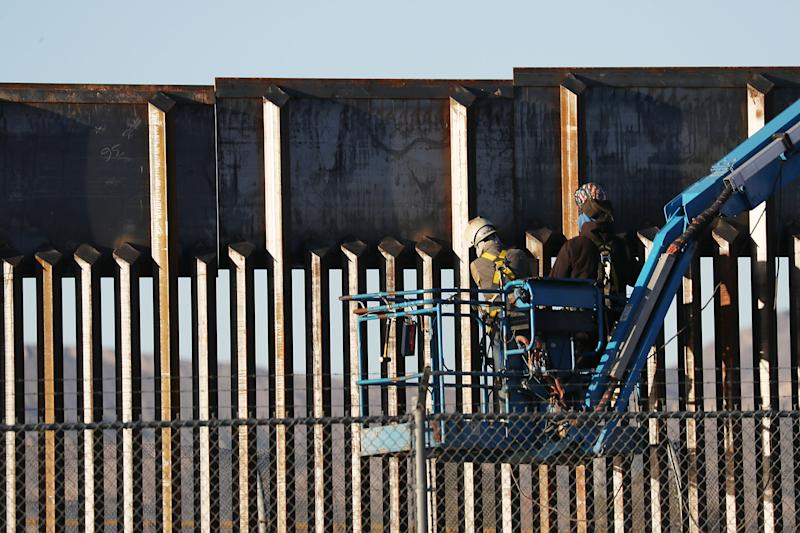 People work on the U.S./ Mexican border wall on February 12, 2019 in El Paso, Texas. | Joe Raedle—Getty Images