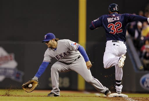 Texas Rangers first baseman Mitch Moreland, left, makes the out against Minnesota Twins' Aaron Hicks (32) during the third inning of a baseball game on Thursday, April 25, 2013, in Minneapolis. (AP Photo/Genevieve Ross)