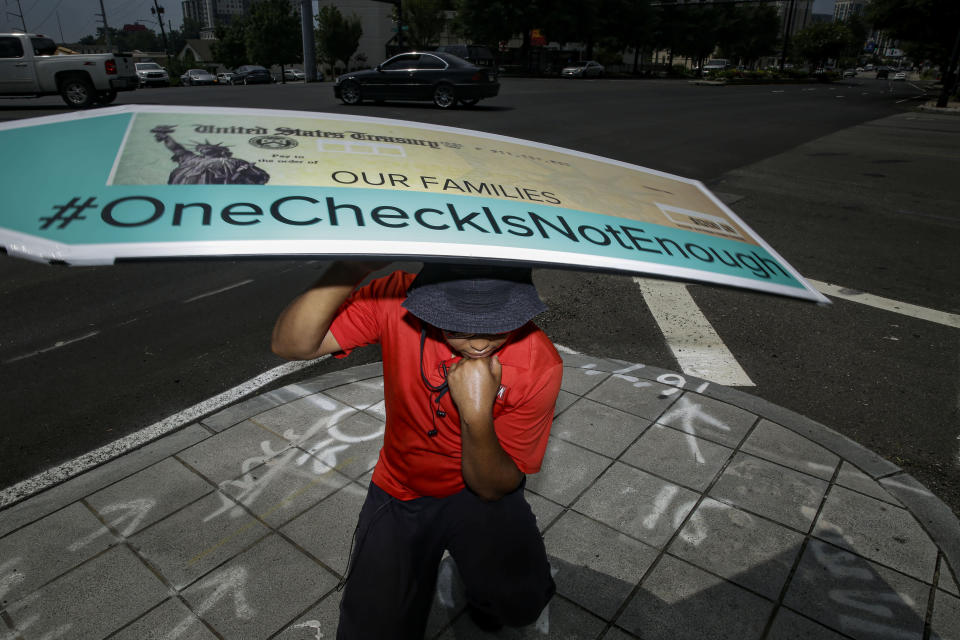 John Miller, 25, of Atlanta, spins a large check sign for the #OneCheckIsNotEnough campaign near Georgia Senator David Perdue's office on Tuesday, Aug. 11, 2020, in Atlanta. The campaign said the large check is to urge politicians to support recurring direct payments in the next coronavirus relief package. (AP Photo/Brynn Anderson)