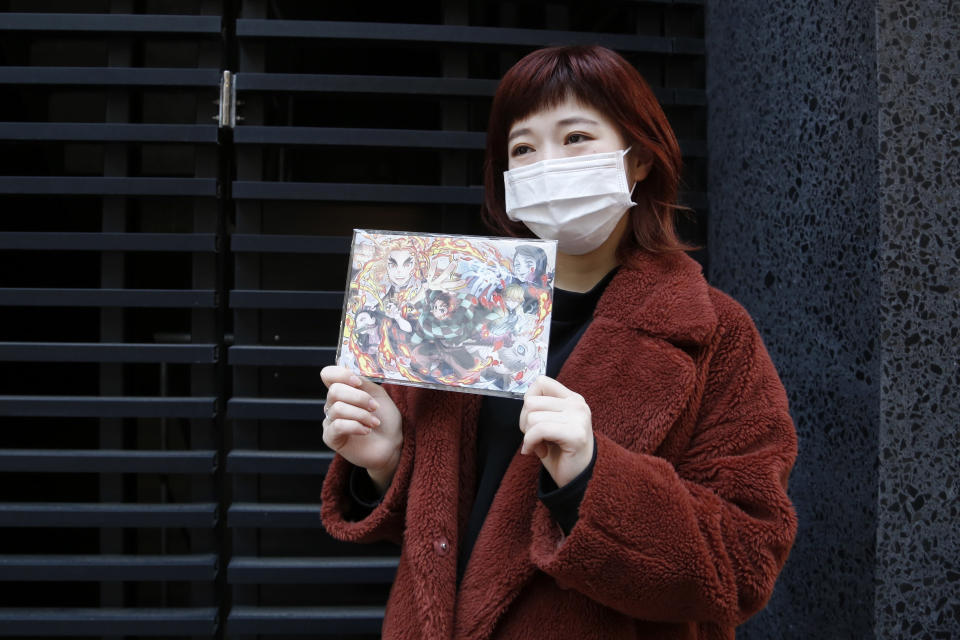 """Japanese hairstylist Akina Nasu wearing a face mask shows a picture she got when she went to see the film """"Demon Slayer,"""" which has become the nation's top-grossing film, and opened in Miami to be eligible for the 2021 Academy Awards, in Tokyo Wednesday, March 3, 2021. Nasu and other fans says they identify with the story because of the hardships and fears during the coronavirus pandemic. (AP Photo/Yuri Kageyama)"""