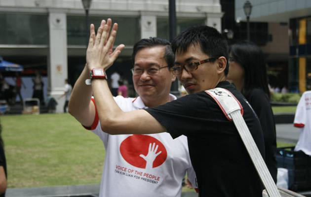Tan Kin Lian posing with a supporter during his lunchtime walkabout at the CBD. (Yahoo!)