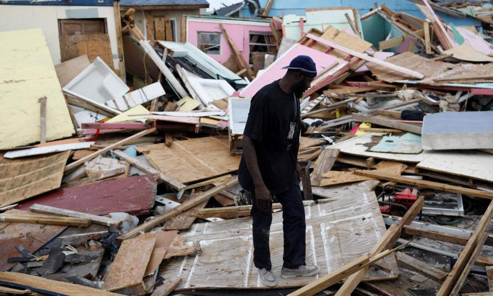 """<span class=""""element-image__caption"""">A man looks for valuables things among the debris at The Mud neightborhood.</span> <span class=""""element-image__credit"""">Photograph: Marco Bello/Reuters</span>"""