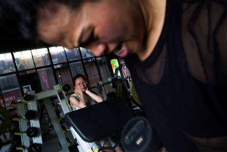 Huang Wensi's sister watches her training at a local gym in Lianjiang, Guangdong province, China, June 30, 2018. REUTERS/Yue Wu