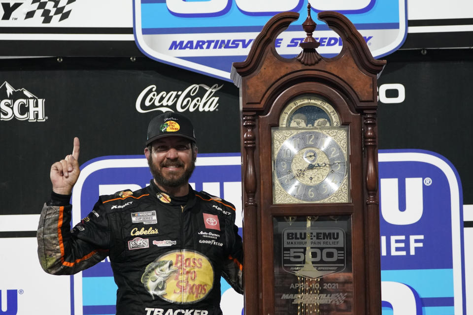 Martin Truex Jr. (19) celebrates with the winners' trophy after winning the NASCAR Cup Series auto race at Martinsville Speedway in Martinsville, Va., Sunday, April 11, 2021. (AP Photo/Steve Helber)