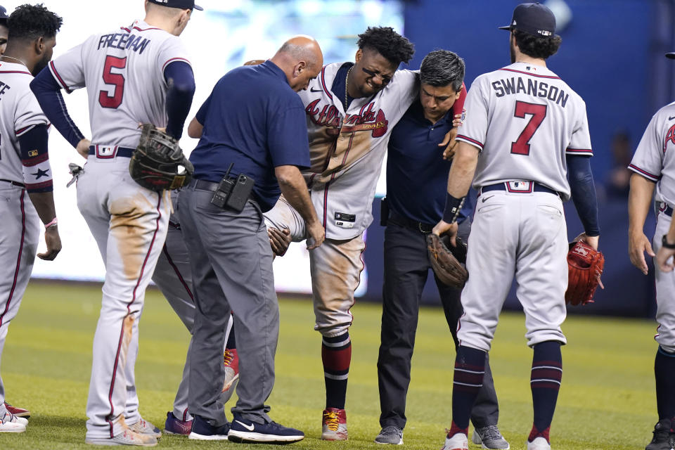 Atlanta Braves right fielder Ronald Acuna Jr., center, is carried to a medical cart after trying to make a catch on an inside-the-park home run hit by Miami Marlins' Jazz Chisholm Jr. during the fifth inning of a baseball game, Saturday, July 10, 2021, in Miami. (AP Photo/Lynne Sladky)