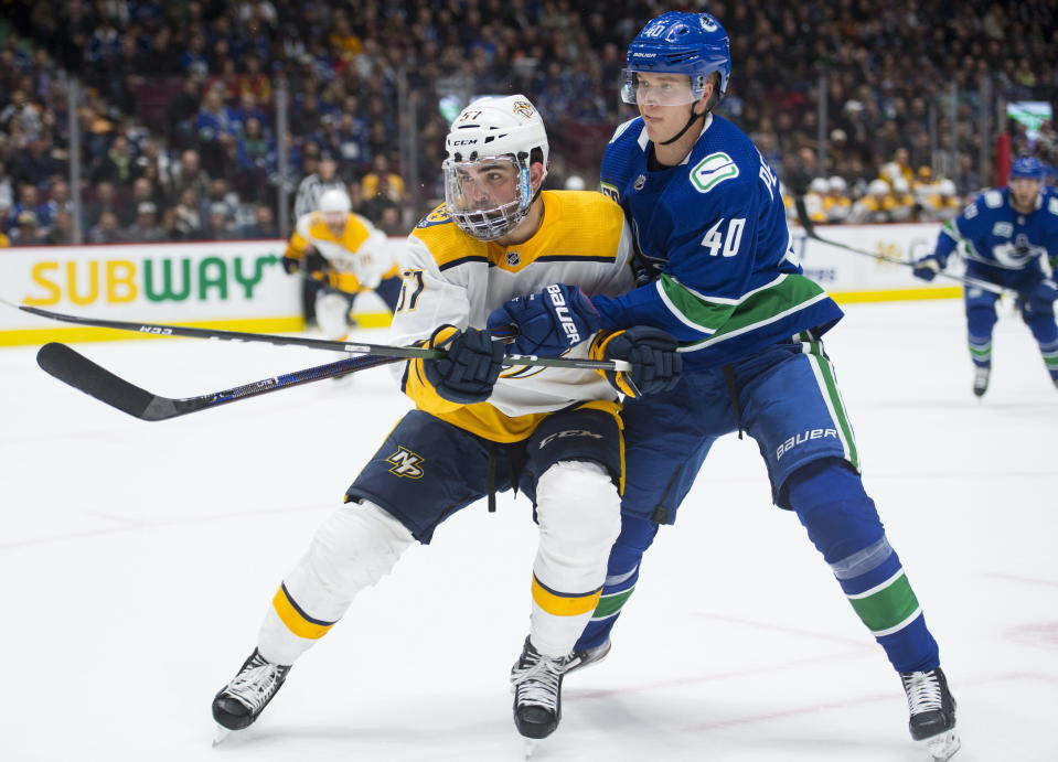 Vancouver Canucks center Elias Pettersson (40) fights for control of the puck with Nashville Predators defenseman Dante Fabbro (57) during the first period of an NHL hockey game Tuesday, Nov. 12, 2019, in Vancouver, British Columbia. (Jonathan Hayward/The Canadian Press via AP)
