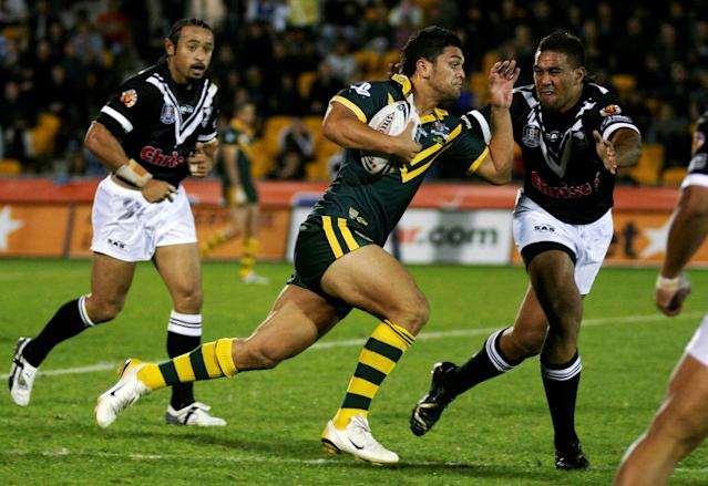 Australia's Karmichael Hunt (C) looks for a way past New Zealand's Frank Pritchard (R) watched by Nigel Vagana during the opening match of the Tri Nations Rugby League tournament in Auckland, New Zealand October 14, 2006. REUTERS/Nigel Marple/File photo