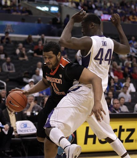 Oregon State's Joe Burton, left, drives past Washington's Darnell Gant during the second half of an NCAA college basketball game at the Pac-12 conference championship in Los Angeles, Thursday, March 8, 2012. Oregon State won 86-84. (AP Photo/Jae C. Hong)