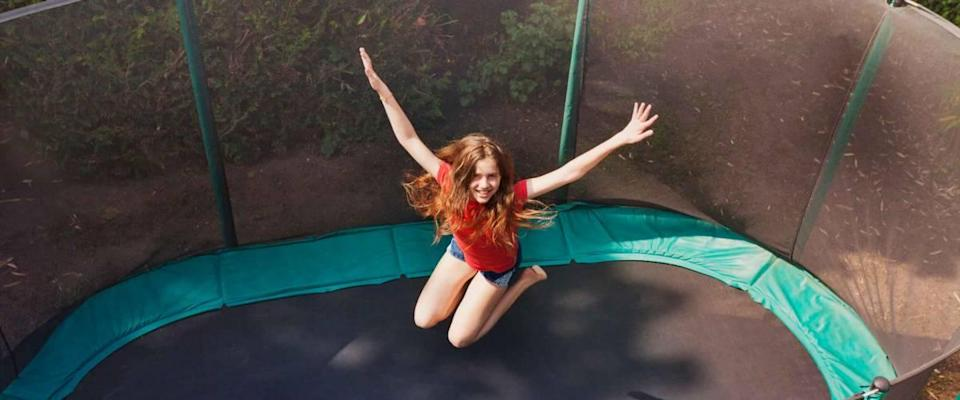 Happy teenage girl jumping on trampoline outdoors