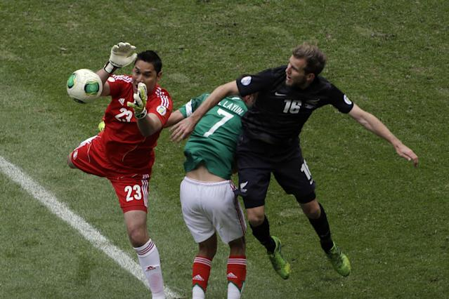 Mexico's goalkeeper Moises Alberto Munoz grabs the ball under pressure from New Zealand's Jeremy Brockie, right, during a 2014 World Cup playoff first round soccer match in Mexico City, Mexico, Wednesday, Nov. 13, 2013. At center is Mexico's Miguel Layun. (AP Photo/Dario Lopez-Mills)