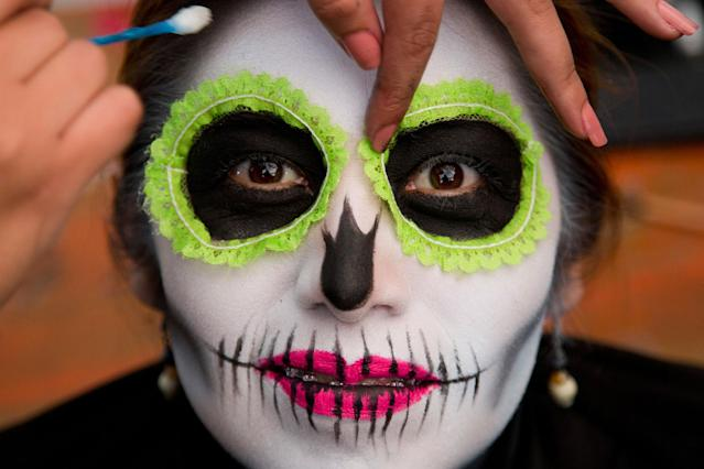 <p>A woman has her make up applied as she waits for the start of a Day of the Dead parade to begin along Mexico City's main Reforma Avenue, Saturday, Oct. 28, 2017. (Photo: Eduardo Verdugo/AP) </p>
