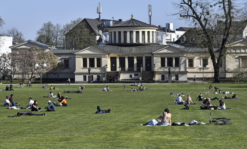 People sit in the warm sun in a park with social distance due to the coronavirus outbreak in Bonn, Germany, Sunday, April 5, 2020. In order to slow down the spread of the coronavirus, the German government has considerably restricted public life and asked the citizens to stay at home. The new coronavirus causes mild or moderate symptoms for most people, but for some, especially older adults and people with existing health problems, it can cause more severe illness or death. (AP Photo/Martin Meissner)