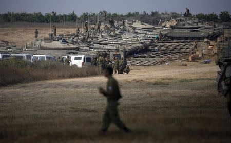 Israeli soldiers gather at a military staging area outside the southern Gaza Strip