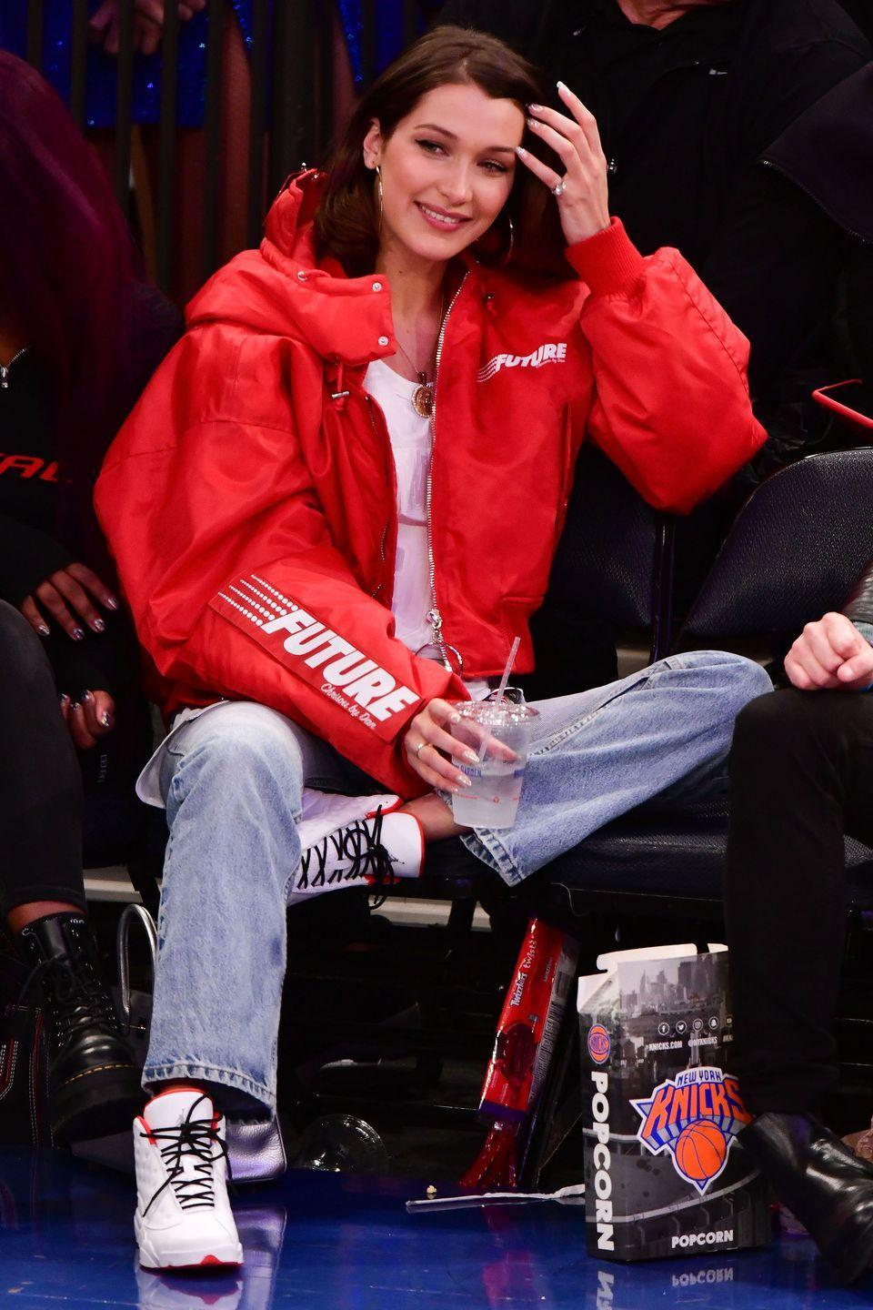 <p>In a Chrisou by Dan bomber jacket, white top, jeans, Jordans, gold hoop earrings, and a gold necklace at a Knicks game in New York City.</p>