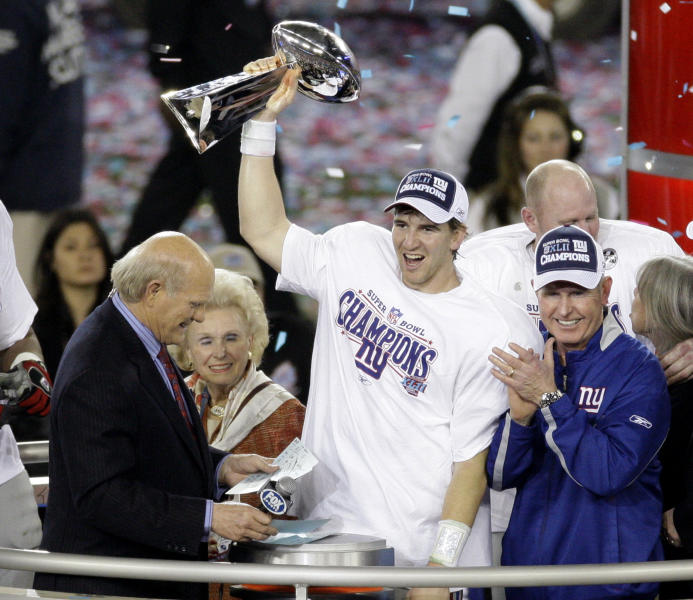 FILE - In this Feb. 3, 2008 file photo New York Giants quarterback Eli Manning, center, holds the Vince Lombardi Trophy as he celebrates with his coach Tom Coughlin, right, after the Giants defeated the New England Patriots 17-14 in the Super Bowl XLII football game in Glendale, Ariz. Manning, who led the Giants to two Super Bowls in a 16-year career that saw him set almost every team passing record, has retired. The Giants said Wednesday, Jan. 22, 2020 that Manning would formally announce his retirement on Friday. (AP Photo/Charlie Riedel)