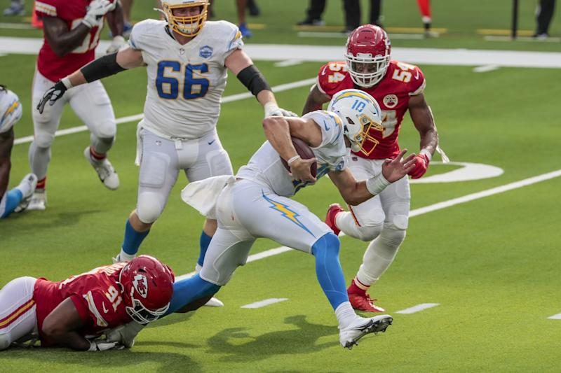 Chargers quarterback Justin Herbert slips away from Chiefs defensive tackle Derrick Nnadi.