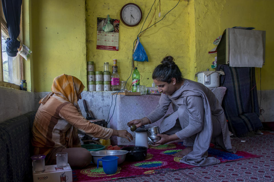 A transgender Kashmiri Khushi Mir, right, helps her mother in the kitchen set up in the corner of a rented room on the outskirts of Srinagar, Indian controlled Kashmir, Friday, June 4, 2021. Until the pandemic, singing and dancing at weddings used to earn Mir enough income to take care of her family. Unable to pay for her rented accommodation, the 19-year-old took a job as a construction worker for 15 days that paid $9.60 a day. Mir has set up a charity, along with four friends, to distribute food kits to members of the transgender community. (AP Photo/ Dar Yasin)