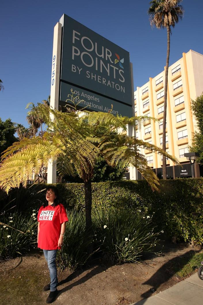 A woman stands near a sign that reads Four Points by Sheraton
